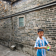 Boy playing in alley at Kat King Wai walled village, New Territories, Hong Kong