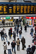 An elevated view of passengers waiting on the station concourse for information from the Departures Board above platforms 11 and 12 at London Victoria railway station, United Kingdom.  The train station is located in central London and is the second-busiest in the capital.