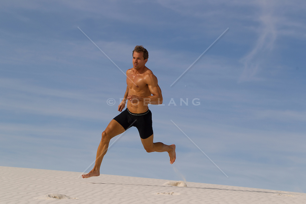 man running on a sand dune in White Sands, NM