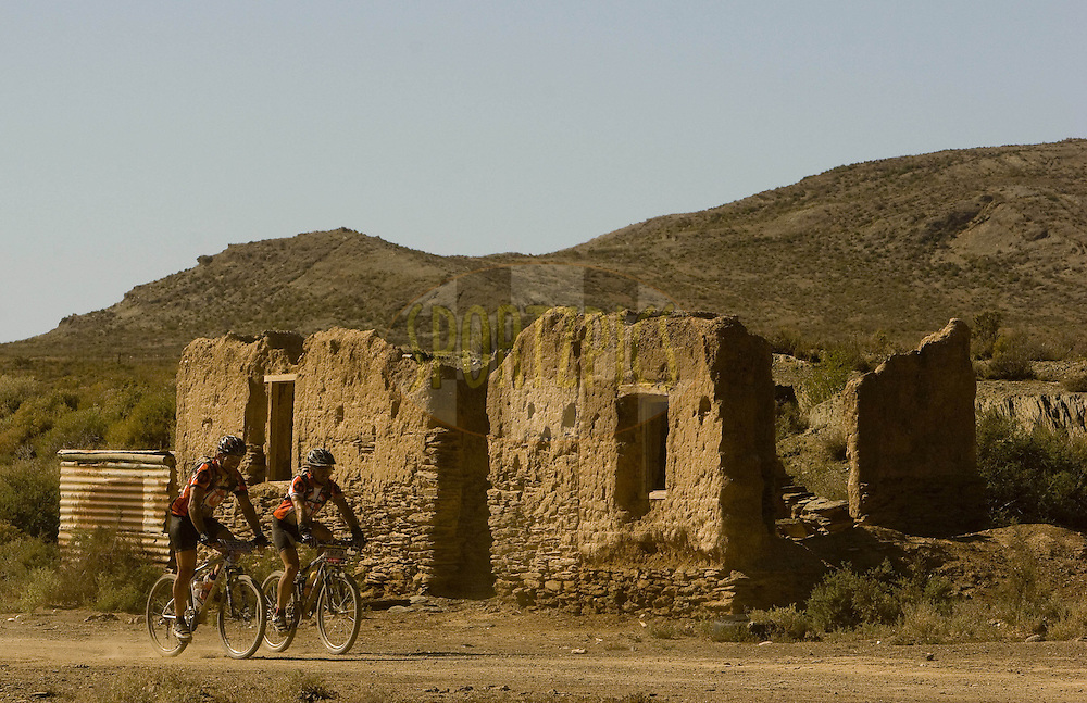WESTERN CAPE, SOUTH AFRICA -  31 March 2008, Riders make their way passed a number of ruins during stage three of the 2008 Absa Cape Epic Mountain Bike stage race from Calitzdorp Spa.to Langenhoven High School in Riversdale, Western Cape, South Africa..Photo by Karin Schermbrucker/SPORTZPICS