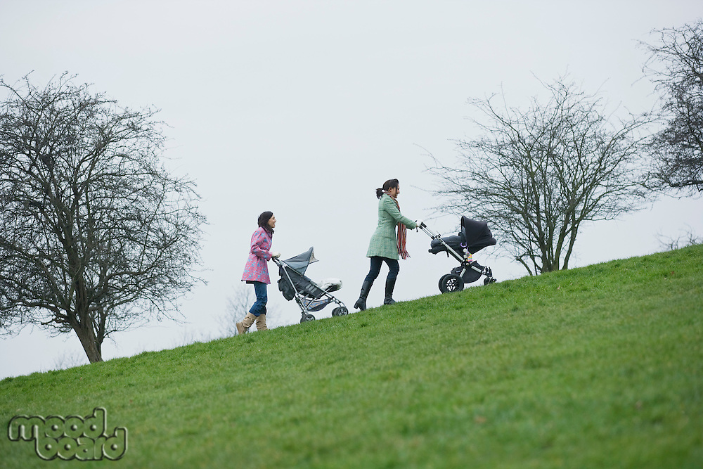 Two mothers pushing stroller uphill
