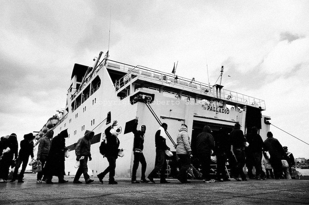 ITALY, Lampedusa : Immigrants that arrived in the last days on the island of Lampedusa board on a ship in the port of Lampedusa that will bring them to a temporary facility on February 14, 2011. Italy said it was planning to deploy its security forces in Tunisia to stop a wave of immigrant arrivals, as coastguards ships continue to intercept boats that are leaving from the North African state. AFP PHOTO / ROBERTO SALOMONE