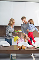 Happy family with children having meal in domestic kitchen