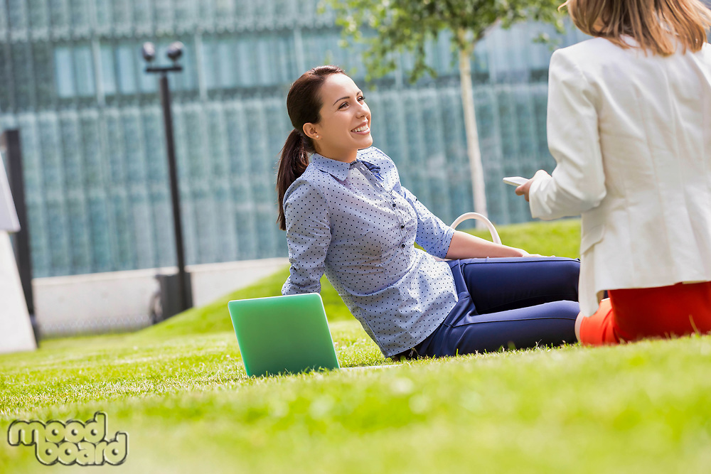 Businesswoman smiling and talking to her colleague while sitting on the grass