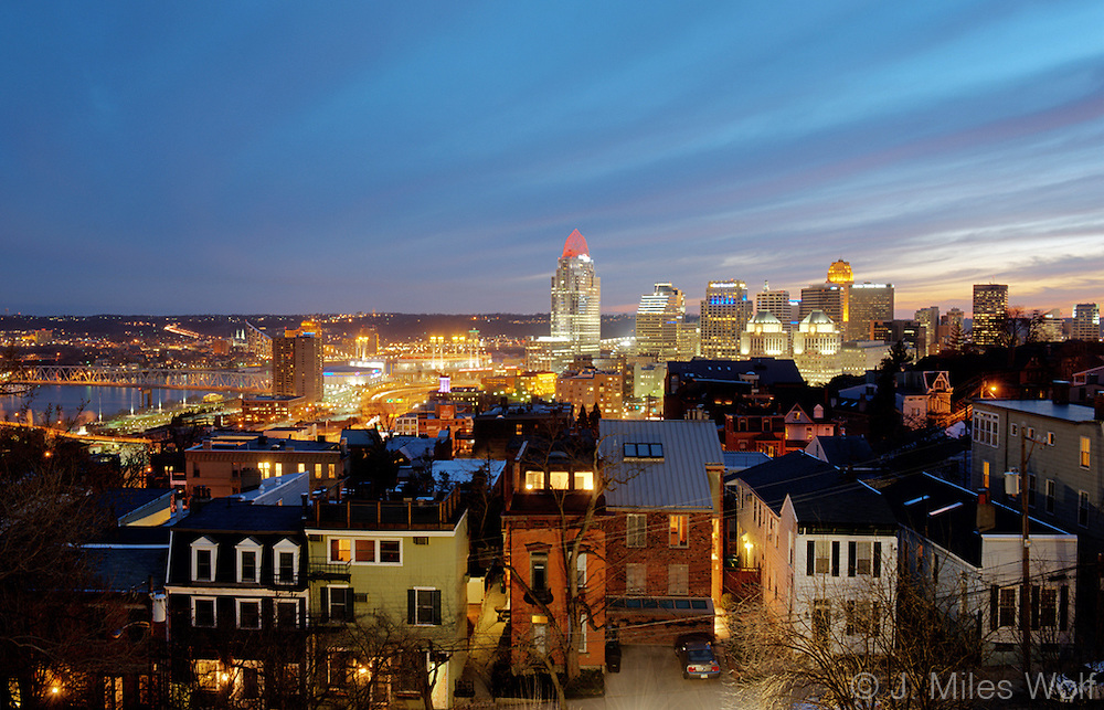Twilight image of a brightly lit Cincinnati Skyline featuring Mount Adams rowhouses in the foreground