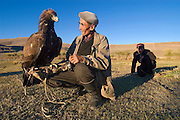 An eagle hunter trains his eagle and teaches his son the ancient Kazakh sport of eagle hunting, Bayan Olgi, Mongolia, Sept 17, 2004.  Kazakhs have hunted with eagles for centuries.  The Eagle Hunting Festival has revived Kazakh culture which was surpressed under Soviet rule.