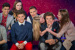 © licensed to London News Pictures. London, UK 26/03/2013. One Direction fans touching new wax figures of the band members at Madame Tussauds London on Thursday 18 April 2013. Photo credit: Tolga Akmen/LNP