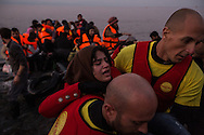 A woman suffering from intense leg pain is carried ashore by lifeguards from the Spanish organization Proactiva from the rubber raft that she and a group of asylum seekers used to cross the Aegean Sea from the North coast of Turkey to the island of Lesvos, Greece on November 16, 2015.