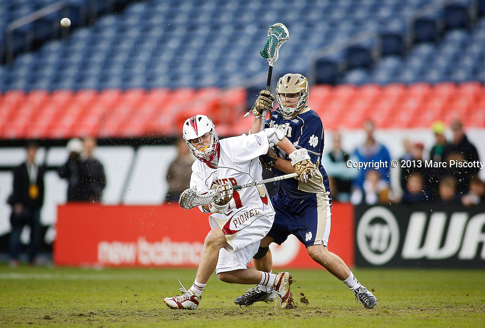 SHOT 3/16/13 5:29:56 PM - Denver's Chris Hampton #20 gets tied up with Notre Dame's Liam O'Connor #31 during their college lacrosse game at the Whitman's Sampler Mile High Classic at Sports Authority Field at Mile High in Denver, Co. on Saturday March 16, 2013. Noter Dame won the game 13-12 in overtime. (Photo by Marc Piscotty / © 2013)
