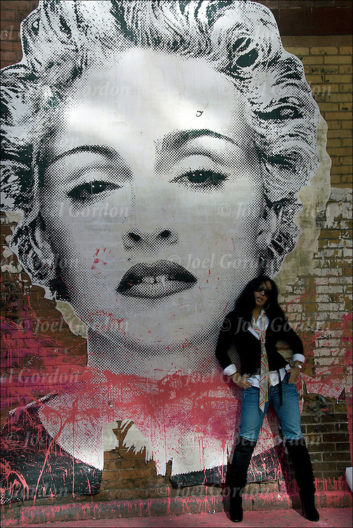 Portrait of a Cougar ( woman who dates younger men ) in the Meatpacking District standing next to wall with two large street art posters of Madonna , by an unknown artist,  and how they are pose themself and interact with the camera in this public place. Street art can be a powerful platform for reaching people in public spaces.