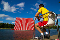 A lifeguard, Ilyas Raja, 18, at the Serpentine's lido stares out across the water at artist Christo's 20m high installation on The Serpentine made from over 7000 barrels, titled The Mastaba, which will be on the Serpentine until 23 September 2018. The Installation is comprised of 7,506 horizontally stacked barrels. It is 20m high, 30m wide and 40m long. Hyde Park, London, June 18 2018.