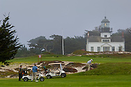Golfers on golf course and Point Pinos Lighthouse in fog, Pacific Grove, Monterey Peninsula, California
