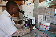 Blood samples being examined under a microscope for HIV and TB at the Bwindi Community Hospital.  These samples are from the Voluntary Counselling and Testing Clinic for HIV and TB. The hospital is in Buhoma village on the edge of the Bwindi Impenetrable Forest in Western Uganda. It serves around 250 000 people from the surrounding area.