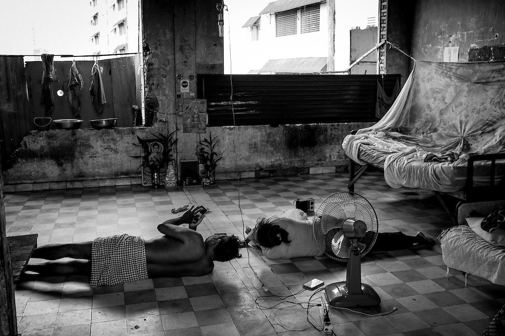 A family lays on the floor of their home as they check their cell phones.The community of Borei Keila in Phnom Penh was once home to hundreds of families before land developer Phanimex bought the property rights to the area and forcefully evicted the residents who refused to accept their compensation package. Those who remained were forced to squat in the remains of the buildings, living in slum-like conditions and without access to plumbing or public electiricity.