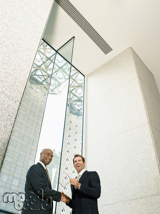 Businessmen shaking hands in office building (low angle view)