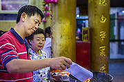 09 FEBRUARY 2014 - HAT YAI, SONGKHLA, THAILAND:  People pray during Lunar New Year in the Tong Sia Siang Tueng temple in Hat Yai. Hat Yai was originally settled by Chinese immigrants and still has a large ethnic Chinese population. Chinese holidays, especially Lunar New Year (Tet) and the Vegetarian Festival are important citywide holidays.     PHOTO BY JACK KURTZ