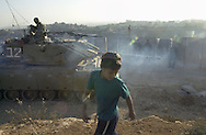 Amir Beit Yakov 9, plays next to a bunker where Israeli soldiers move a tank in to position for the evening in front of the West Bank town of Ramallah where Palestinian gunmen shoot in to the Jewish settlement of Psagot Monday Dec. 4, 2000.