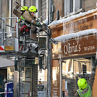 Freezing Weather in Perth....<br /> Continuing freezing temperatures have led to the build up of ice on buildings, Firefighters in Perth are pictured responding to a 999 call to deal with icicles on buildings on North Methven Street which was closed while the firefighters made the buildings safe.  Pictured are firefighters Steven Reid (right) and Murray Smith on the aerial platform breaking off the ice.<br /> Picture by Graeme Hart.<br /> Copyright Perthshire Picture Agency