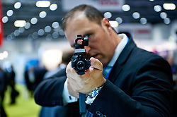 DSEI arms fair in London.<br /> A businessman tries one of the rifles during the 2013 edition of DSEI at Excel London, United Kingdom. Tuesday, 10th September 2013. Picture by Piero Cruciatti / i-Images