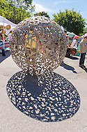 "Huntington, New York, U.S. 24th August 2013. STEVEN ZALUSKI, performance artist, is walking around in his rolling metal sculpture ""Sphere of Hope"" at the art event ""Off the Walls"" Block Party, by SPARKBOOM, a Huntington Arts Council project created to help emerging artists, showcase talents, and help its artistic family network. The sculpture of human shapes welded together has a round opening big enough for a person to enter, Zaluski's studio is in Ronkonkoma."