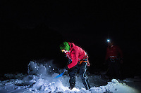 Two male mountaineers dig a snow cave on Glacier Blanche on a cold winter night.