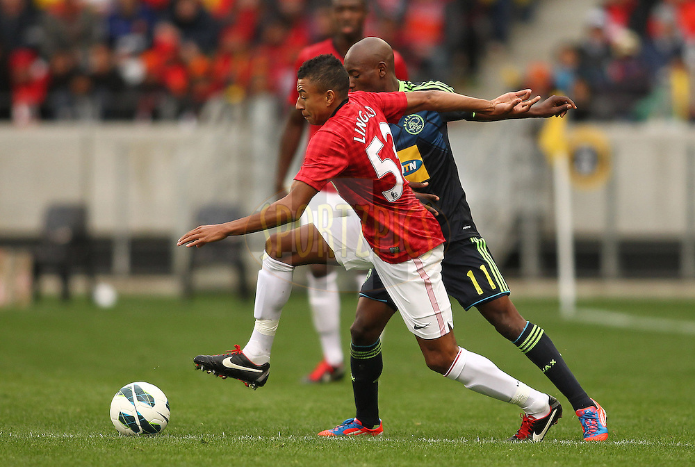 Jesse Lingard of Manchester United and Khama Billiat of Ajax Cape Town challenge for possession during the Football Invitational 2012 match between Ajax Cape Town and Manchester United held at Cape Town Stadium on 21 July 2012 in Cape Town, South Africa..Photo by Shaun Roy / Sportzpics