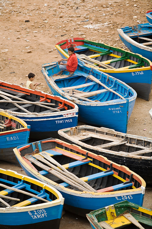 Children sitting on colorful fishing boats on the beach in Taghazout, Morocco.Taghazout is a popular surfing town north of Agadir.