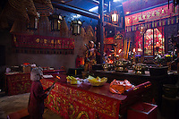 Woman worships with offerings of incense at Tin Hau Temple, Hong Kong