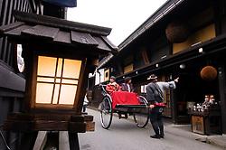 Tourists on rickshaw tour of historic Takayama in Japan
