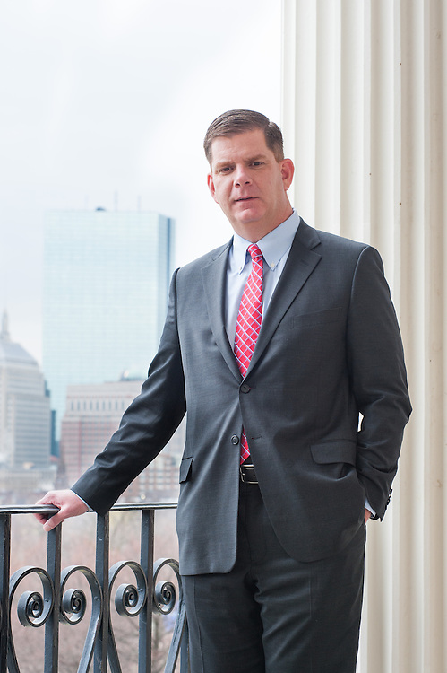 Mayoral candidate Marty Walsh on the Statehouse balcony with the Hancock Tower over his shoulder.