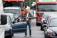 Nederland Rotterdam 30-09-2010 20100930..File op de rijksweg A16 op de oosterlijke ring, lange rijen met auto's staan stil. Man is uit auto gestapt en tikt (waarschijnlijk) een sms op zijn mobiel. Handsfree bellen, telefoneren, mobieltje, handen vrij, gsm, smart phone, communiceren, communicatie, mobiele telefoon.   Traffic jam. Holland, The Netherlands, dutch, Pays Bas, Europe ..Foto: David Rozing