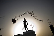 JORDAN, Amman : A Jordanian boy flies a home made kite on a rooftop in Amman on March 31, 2011. ALESSIO ROMENZI
