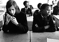 Secondary school pupils sitting in class looking tense but bored.
