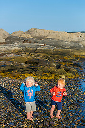 Twin boys play on East Gosling Island in Casco Bay, Harpswell, Maine.