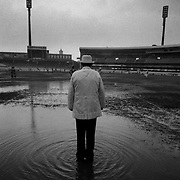 An Australian Rules umpire stands in the rain during a junior match at the Sydney Cricket Ground.