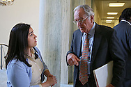 Senator Tom Harkin (D-IA) talks with Deputy Press Secretary Mandy McClure in the Rayburn House Office Building on his way to a reception in Washington, DC on Wednesday, April 10, 2013.