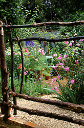 Brick paved town garden filled with roses and delphiniums, framed by homemade recycled wooden fence