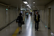 A Japanese salaryman or male office worker and female office worker walk through corridors in Ikebukero train station in Tokyo, Japan. Friday September 28th 2018