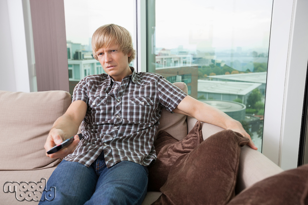 Relaxed mid-adult man watching television on sofa at home