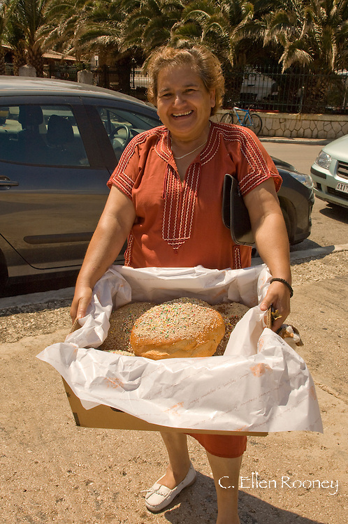 A woman carrying  large loaves of bread in Vathos, Ithaca, The Ionian Islands, Greece