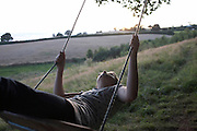 An eleven year-old girl swings with head thrown backwards in a field in Herefordshire, England. It is an image of care-free youth, of a free-spirit and without a care in the world. The young lady gazes skyward as the swing takes her on an upward trajectory, the sun sinking behind distant trees, a scene of splendid inner-peace and tranquillity, disturbed only by the creaking of the rope on the tree above that supports her as she rides. She is staying at this small camp site where tipis and yurts is the theme of this eco-friendly and carbon-neutral holiday.