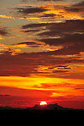 A sunset colors the sky during monsoon season in the Sonoran Desert,Tucson, Arizona, USA.