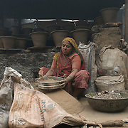 A potter's wife siffting clay. THE KUMBHAR potters are probably the oldest community in Dharavi and unlike the rest of Dharavi which is famous for recycling things everyone throws away, the Kumbhars create the new.