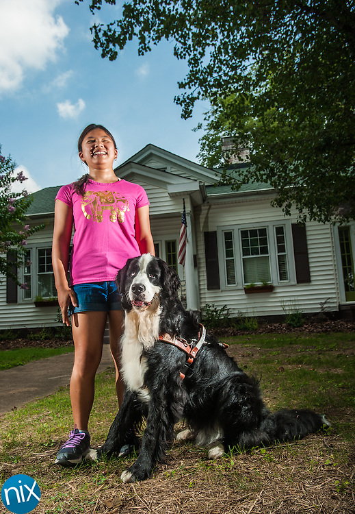 Hope Bovard, 13, with her guide dog Hibou at her home in Concord. Bovard is legally blind and received Hibou through the MIRA Foundation USA.