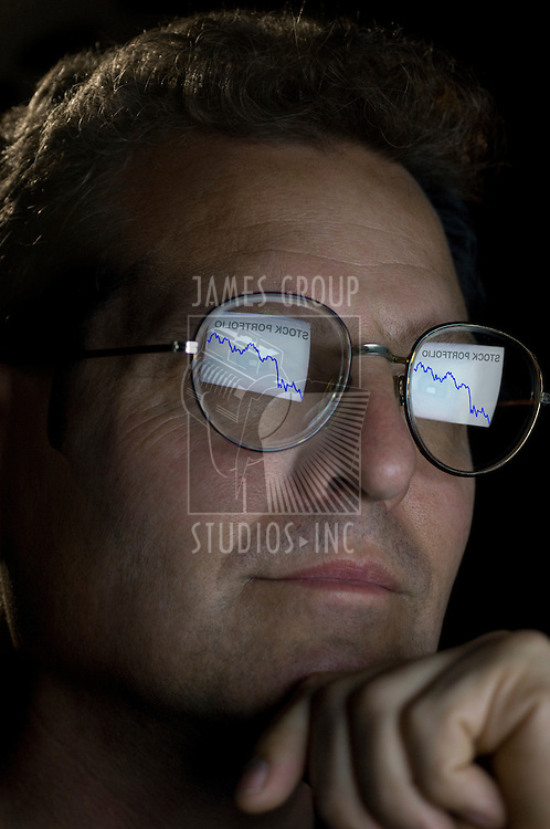 close-up of an investor with an ascending stock portfolio graph reflected in his glasses.