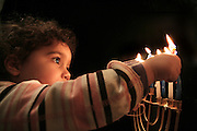 Child lighting the candles in a Chanukkah Menorah