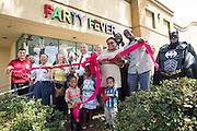Mayor Jose Esteves and members of the Milpitas Chamber of Commerce pose for a photo before cutting the ribbon during the Milpitas Chamber of Commerce Ribbon Cutting Ceremony at Party Fever in Milpitas, California, on July 31, 2014. (Stan Olszewski/SOSKIphoto)