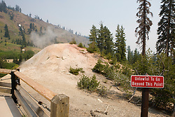 A red warning signs instructs visitors that it is unlawful to go past as steam rises from the Sulphur Works hydrothermal area in Lassen Volcanic National Park, California, USA.