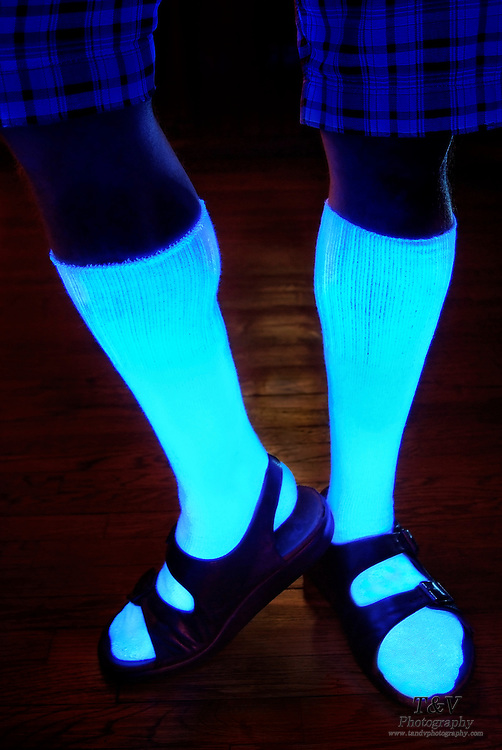 Man wearing shorts and sandals with glowing socks.Black light