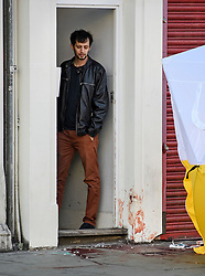 © Licensed to London News Pictures. 13/09/2019. London, UK. A resident stands over pools of blood outside the doorway to his property, at the scene on Camden HIgh Street in North London where a man was last night stabbed to death and another man remains in hospital with a knife wound. Photo credit: Ben Cawthra/LNP